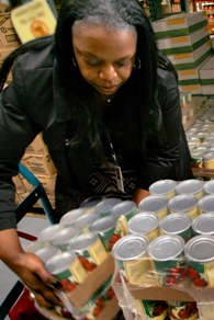 A pantry volunteer readies canned tomatoes for distribution